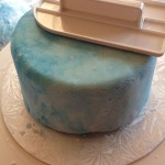 Sky blue (Ameri-Colour) was used; I was able to get a marbled effect after much rolling and adding a few drops of colour in sequence. If you do not have a fondant smoother, using your strong hand guided by your weak hand would work too.