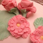Close up on carnations, roses and leaves. Yellow buttercream was piped onto the centre of the carnations.